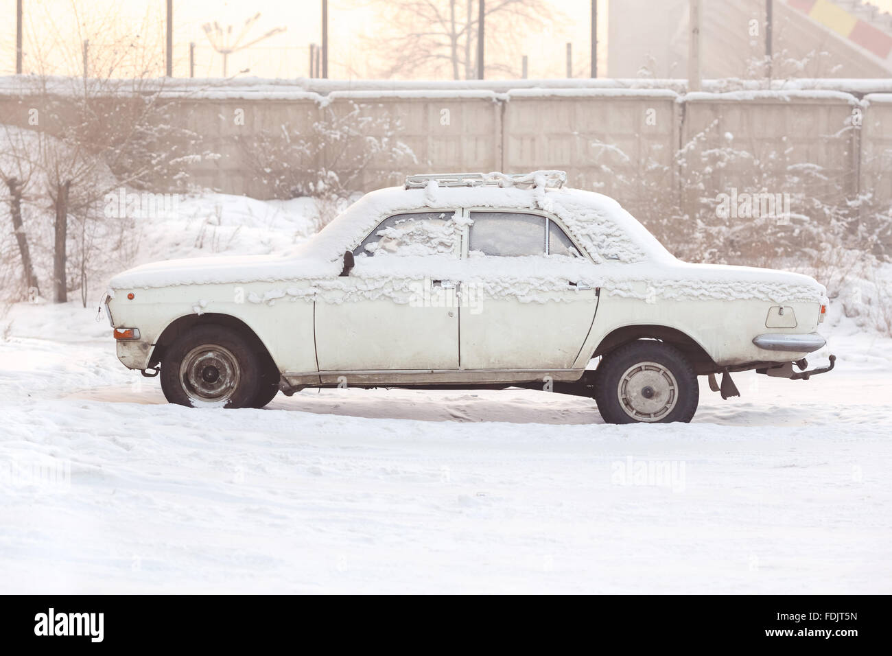 Abandoned car covered with snow in winter at sunset, warm tones, side view. Rusting, recycling, metal processing, - Stock Image