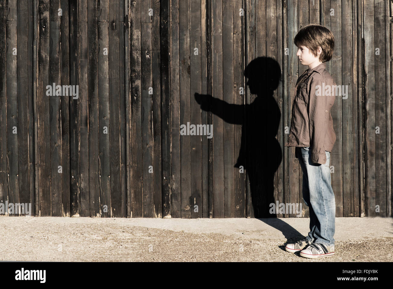 Boy standing next to a wooden fence with alter ego shadow - Stock Image