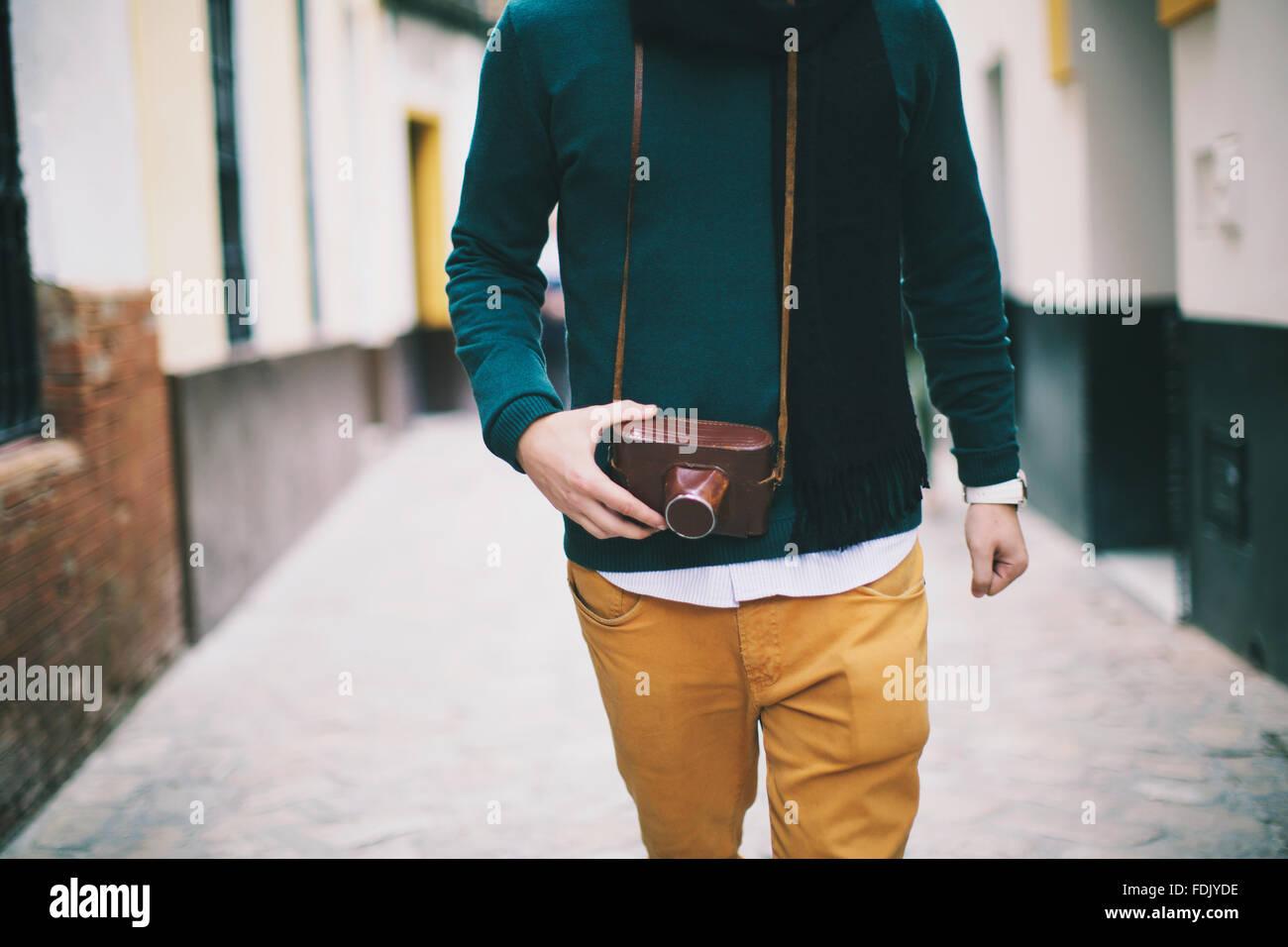Man walking down street, holding vintage retro  camera, Seville, Spain - Stock Image