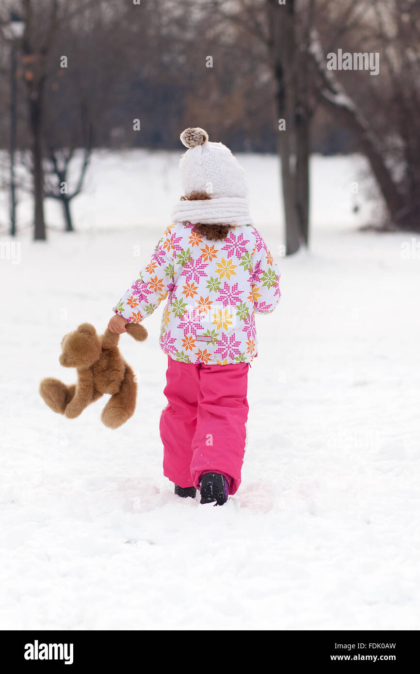 Rear view of girl walking with teddy bear on a winter day - Stock Image