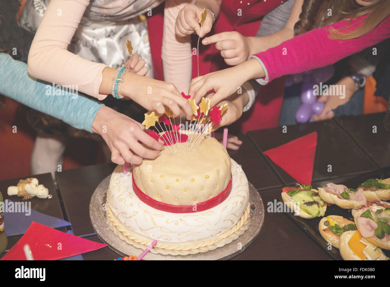 Four children decorating birthday cake - Stock Image