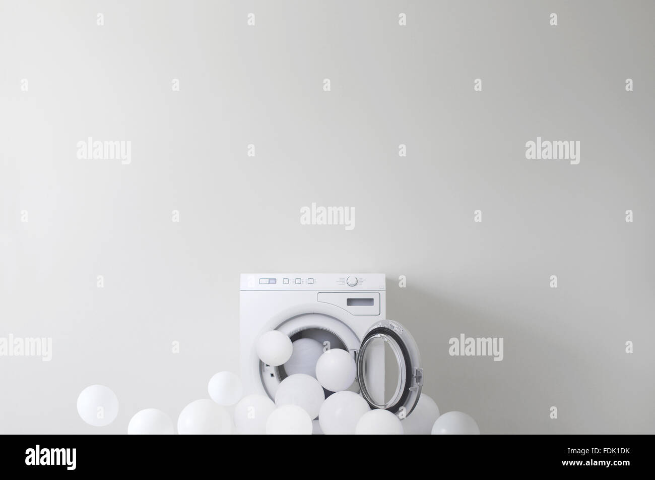 Conceptual washing machine leaking soap suds - Stock Image