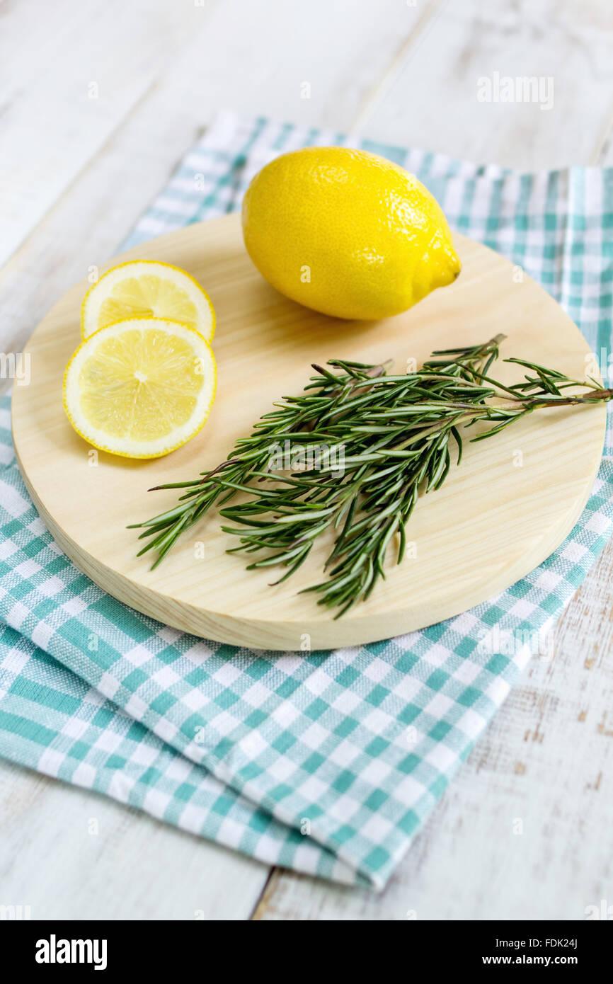 Lemon and rosemary on chopping board Stock Photo