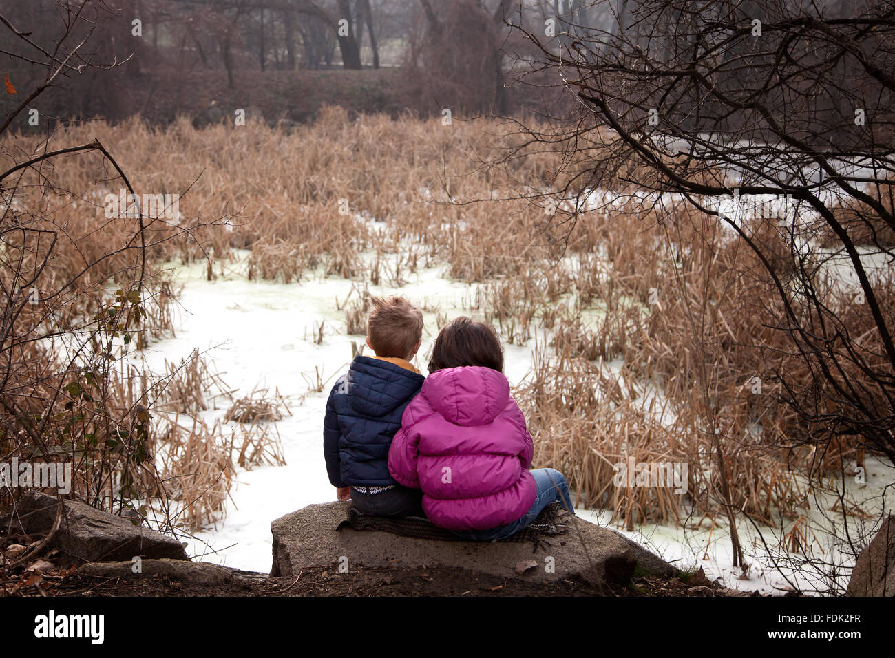 Boy and girl sitting on rock in forest, Sofia, Bulgaria - Stock Image