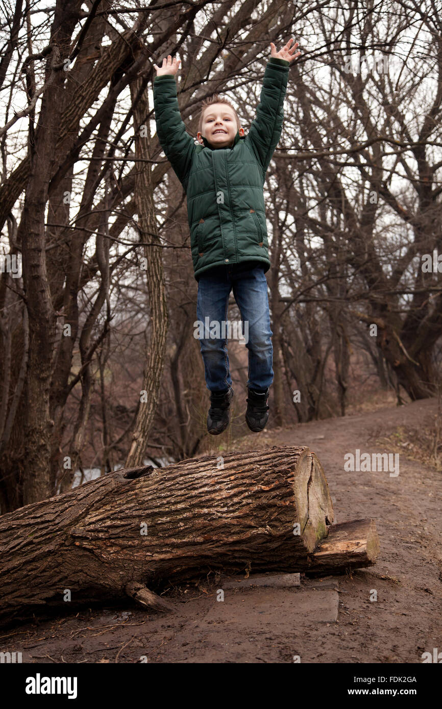 Boy jumping off tree trunk in forest, Sofia, Bulgaria Stock Photo