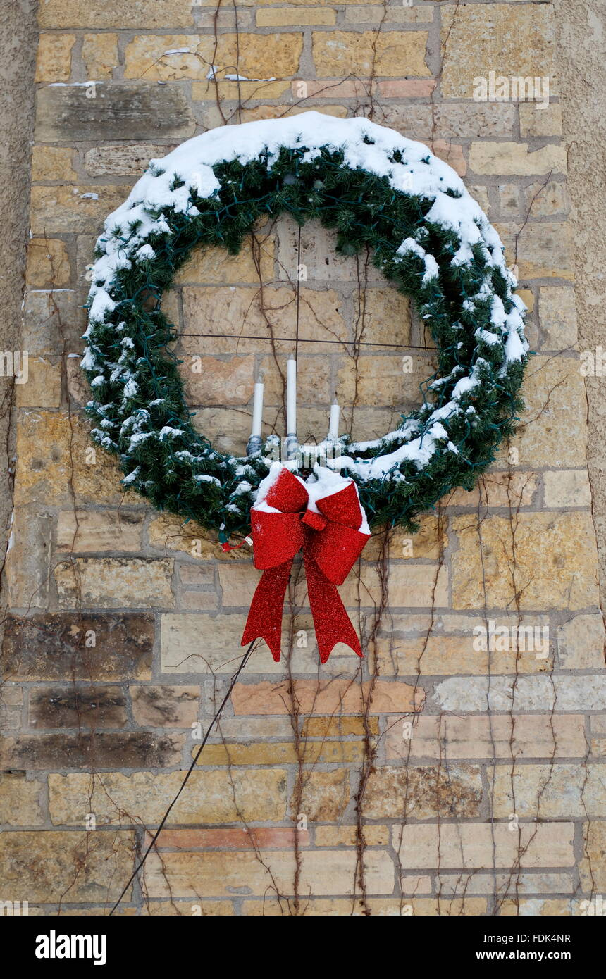 wreath with red bow hanging on a brick wall