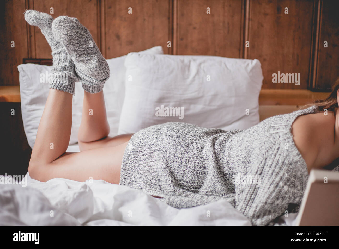 Side view of a woman lying on a bed reading a book Stock Photo