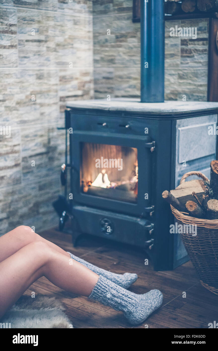 Woman sitting in front of a wood burning stove - Stock Image