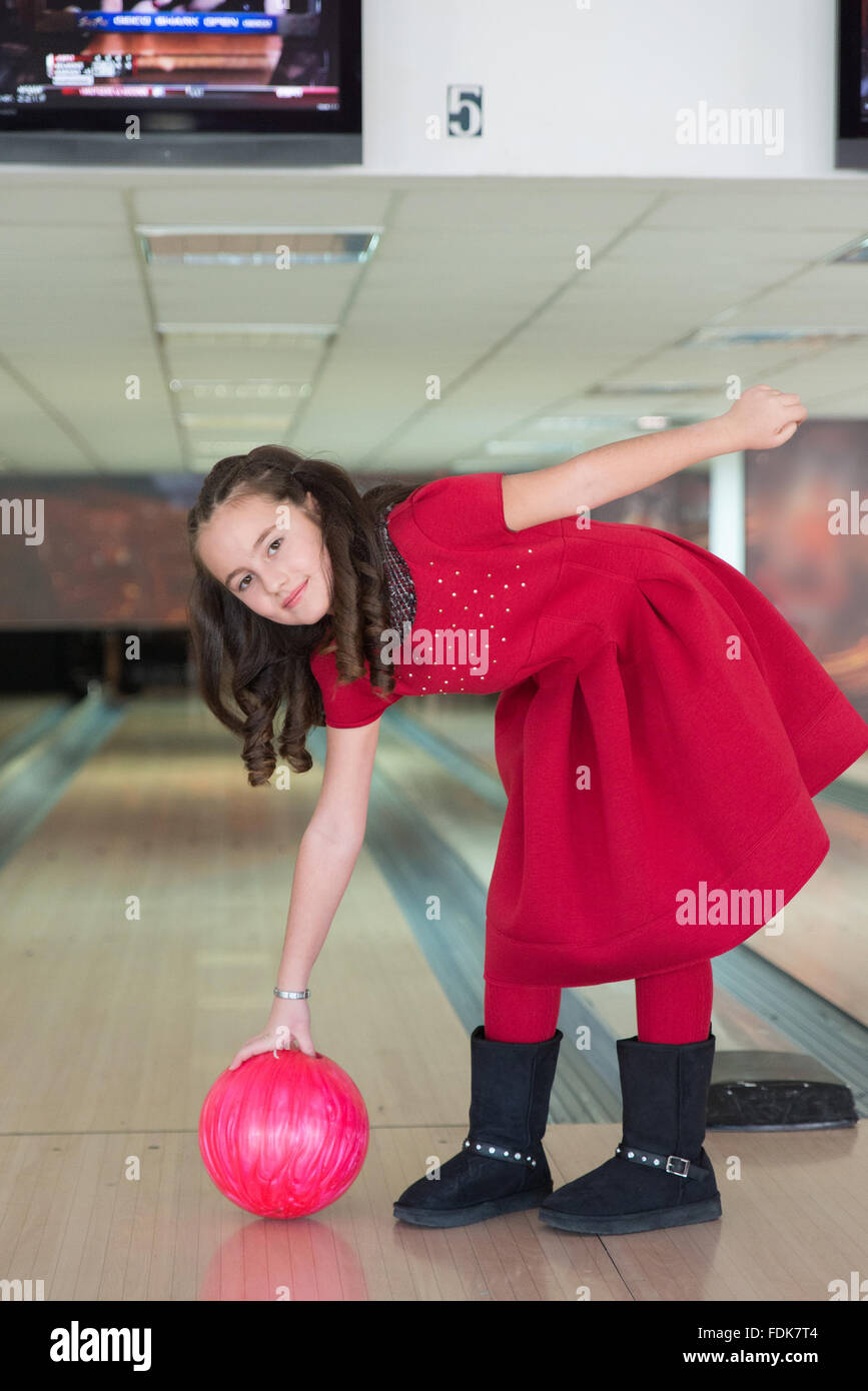 Girl with bowling ball at bowling alley - Stock Image