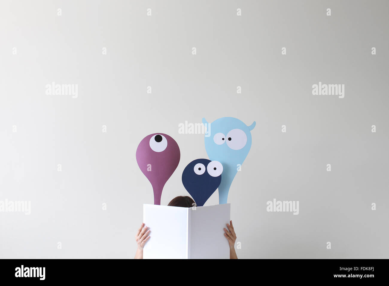 Woman reading book with friendly monsters popping up - Stock Image