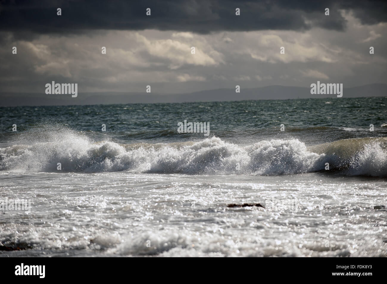 Waves and dark clouds off Pennard, Gower, Wales. - Stock Image