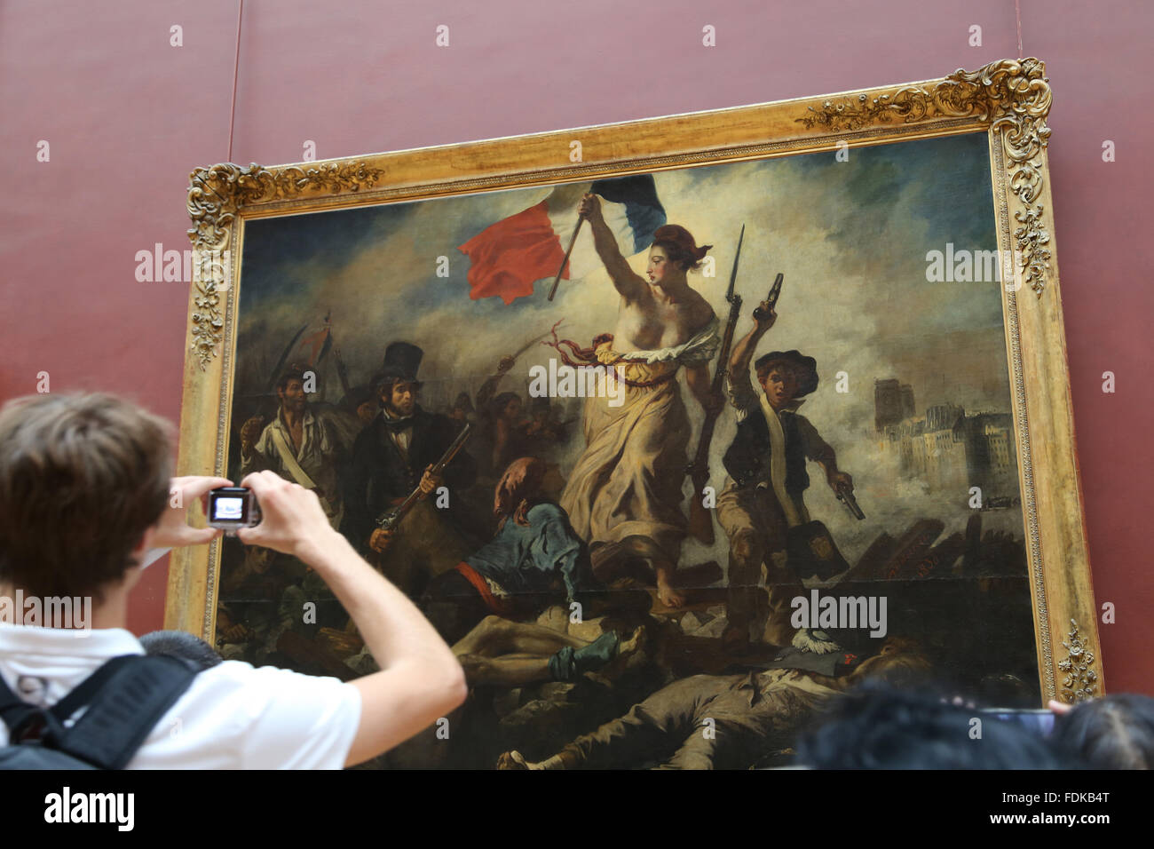 Tourist inside Louvre Museum.  Liberty leading the people, 1831. By Eugene Delacroix. Paris. - Stock Image