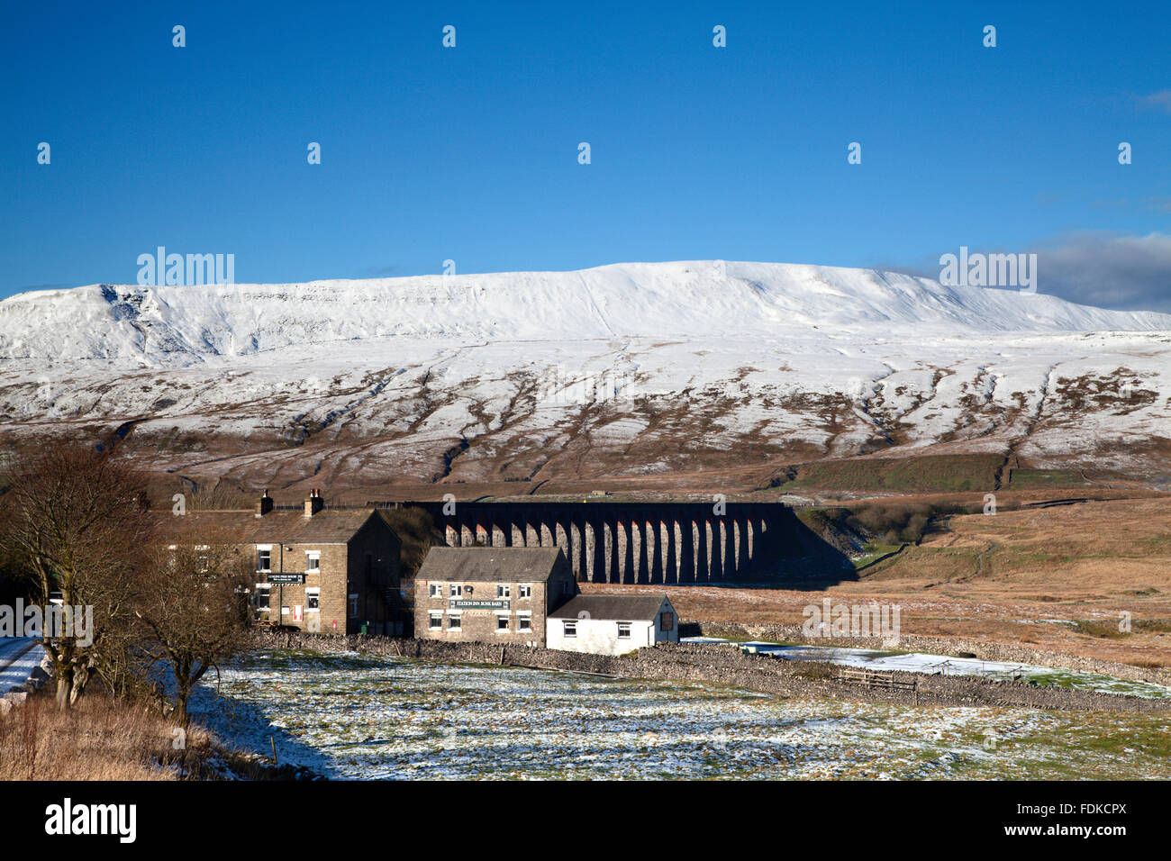The Station Inn and Ribblehead Viaduct below the Snowcapped Peak of Whernside Ribblehead Yorkshire Dales England - Stock Image