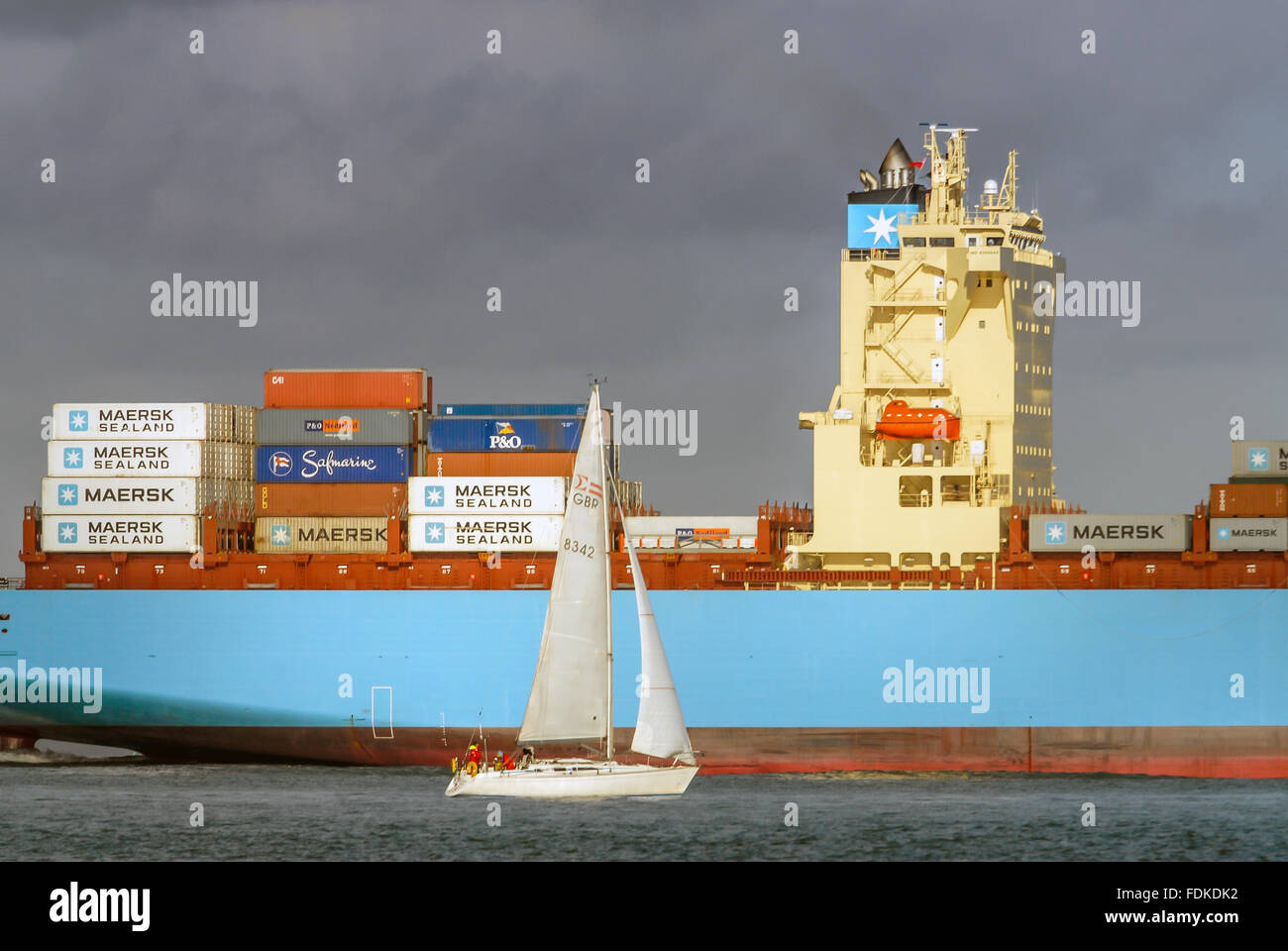 A Maersk container ship loaded with cargo negotiating the narrow channels of The Solent at the Isle of Wight. Stock Photo