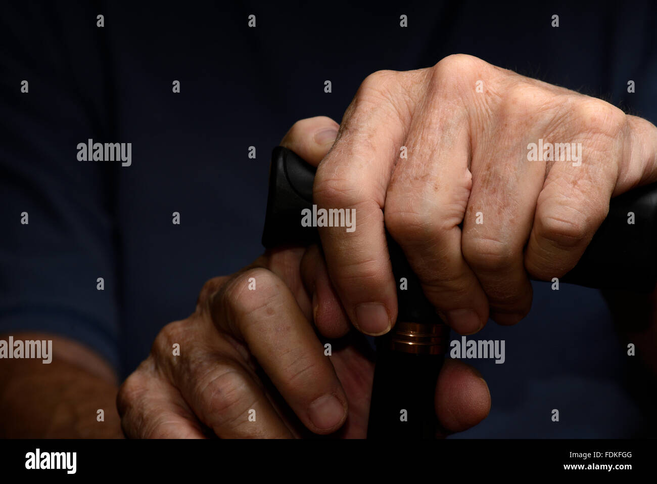 Hands of an elderly woman with chronic health and medical issues grasp a walking cane. - Stock Image