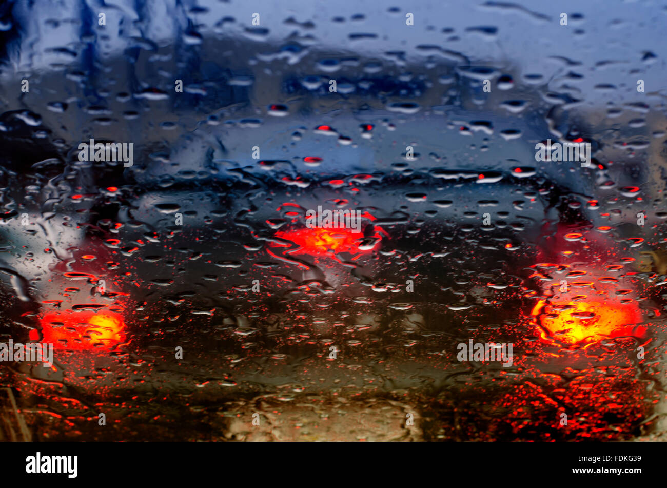 Taillights of a car seen through windscreen on a rainy day - Stock Image