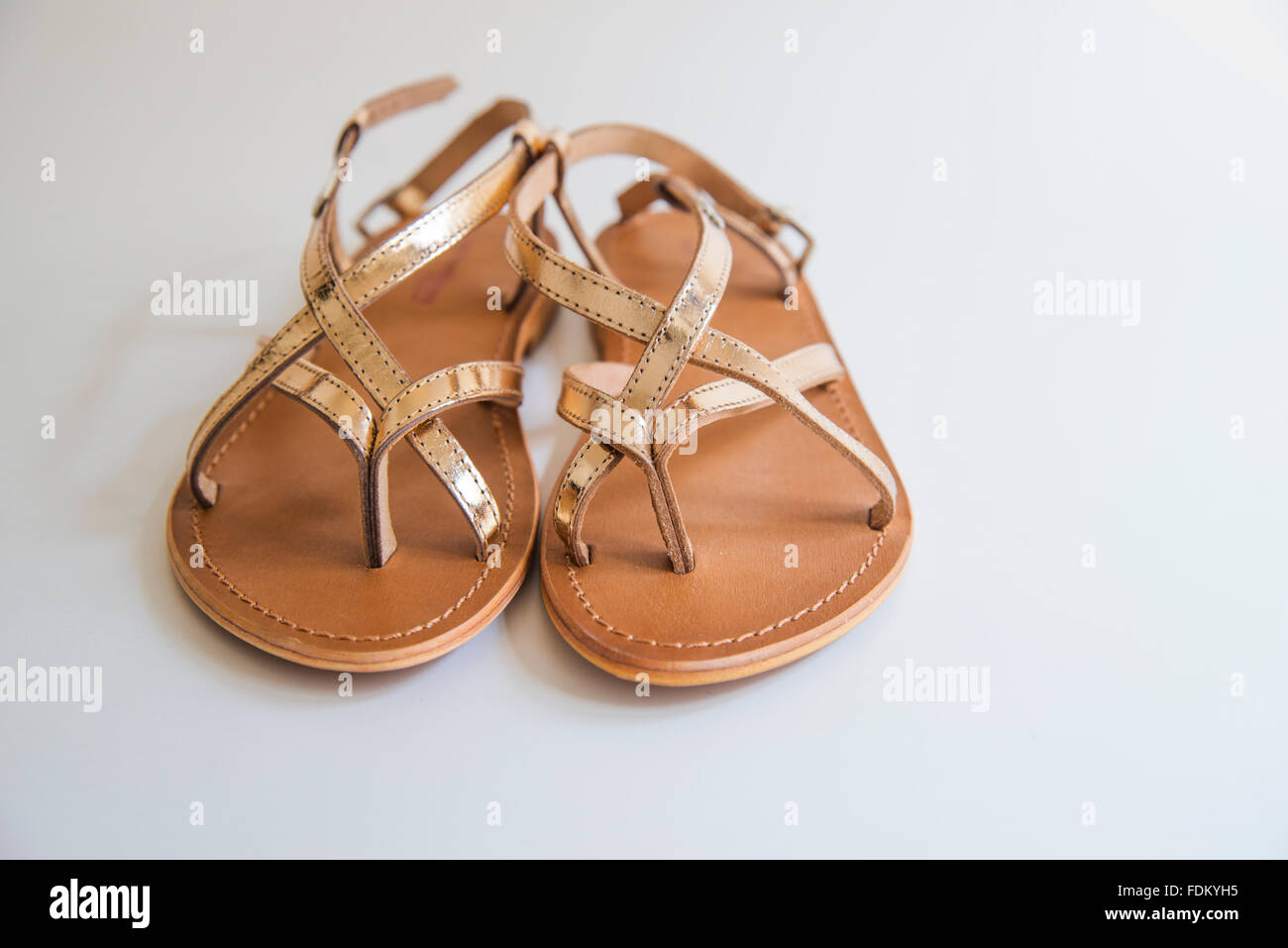 Pair of golden sandals. - Stock Image