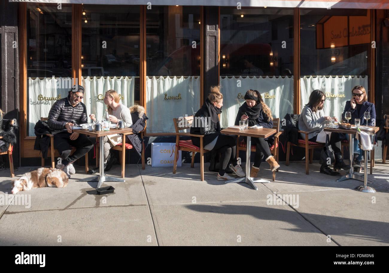 Alfresco dining in winter outside New York City restaurant dog - Stock Image
