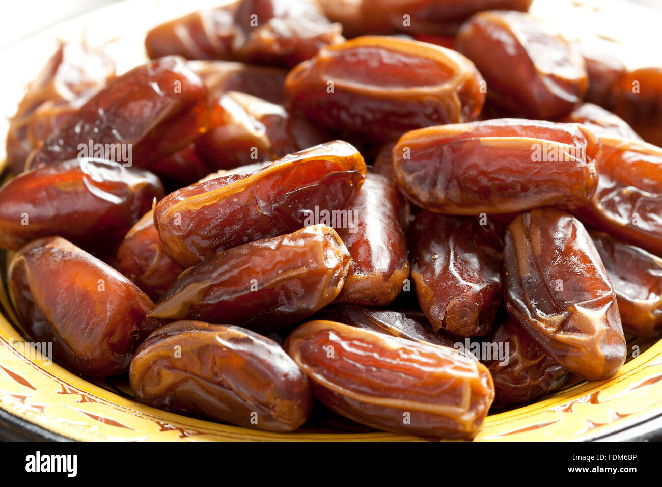 Heap of preserved dates on a dish close up - Stock Image