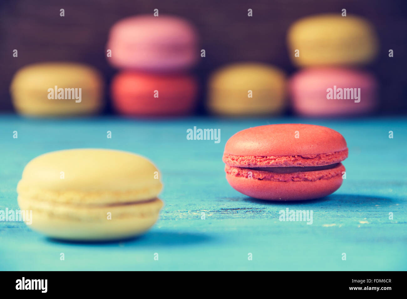 some appetizing macarons with different colors and flavors on a blue rustic wooden surface - Stock Image