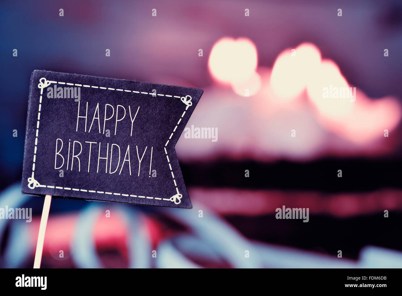 closeup of a black flag-shaped signboard with the text happy birthday, and a birthday cake with lit candles in the - Stock Image