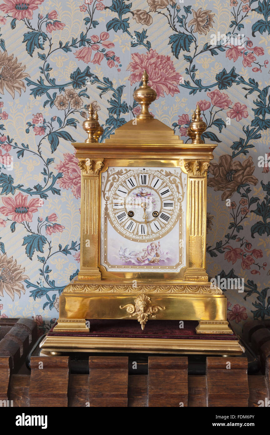 Late nineteenth-century gilt-metal clock by FH Goulding, in the Bedroom at Knightshayes Court, Devon. - Stock Image