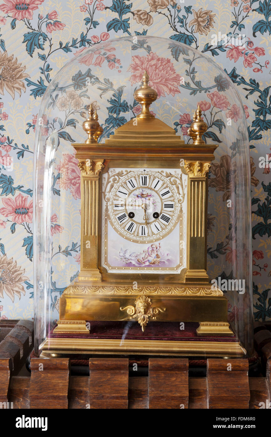 Late nineteenth-century gilt-metal clock by FH Goulding, under a glass dome, in the Bedroom at Knightshayes Court, - Stock Image