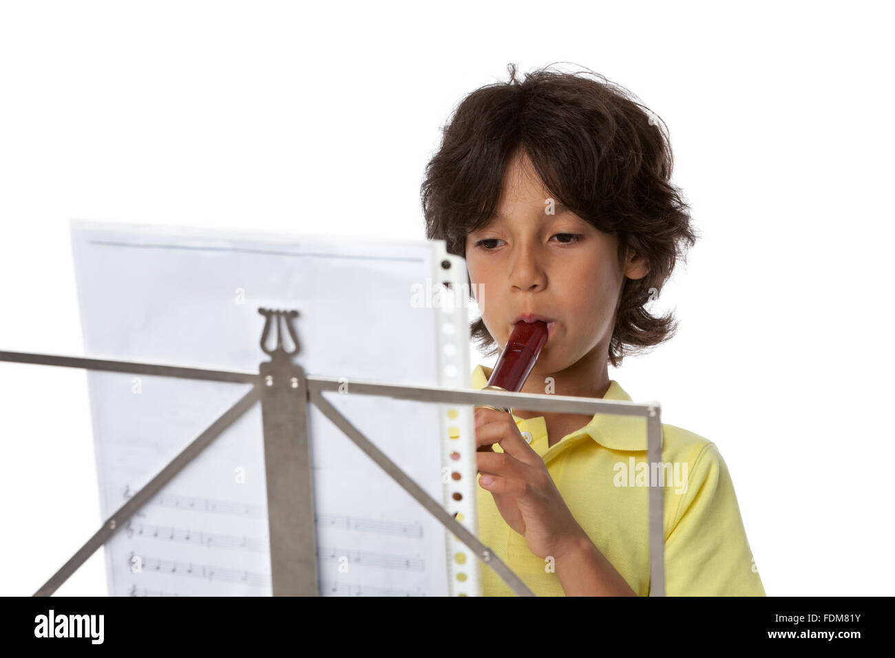 Little boy is playing the recorder on white background - Stock Image