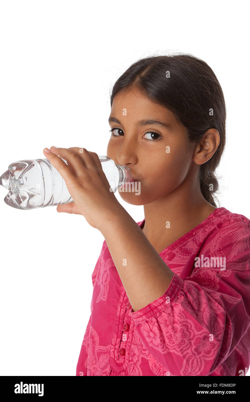 Young teenage girl drinking fresh water from a bottle on white background - Stock Image