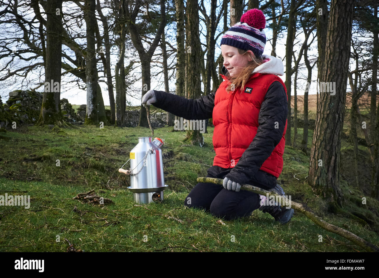 A girl places a stick into a Kelly Kettle wood stove outdoors in the woods - Stock Image