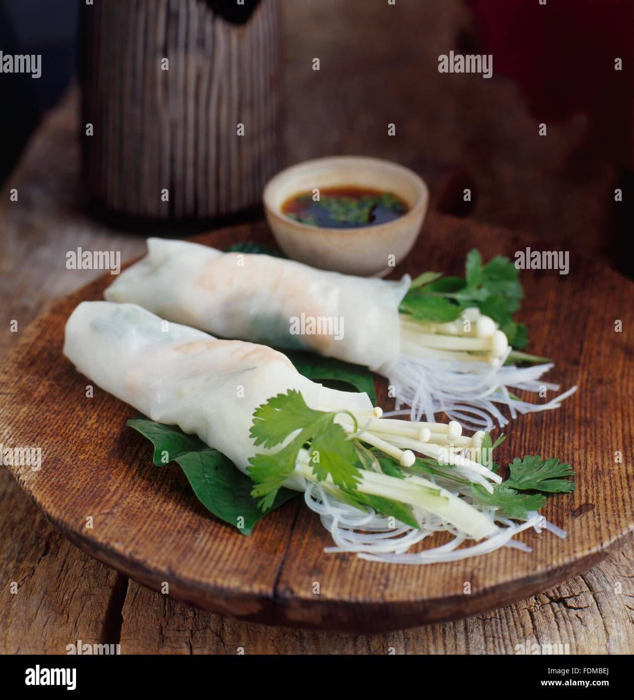 Rice paper wrappers stuffed with enoki mushrooms, prawns and herbs, served on wooden board, with a dip - Stock Image