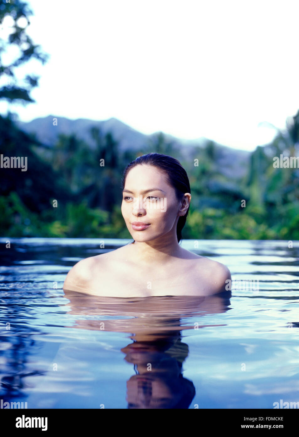 A woman relaxes in the infinity pool at The Farm at San Benito, Philippines. - Stock Image