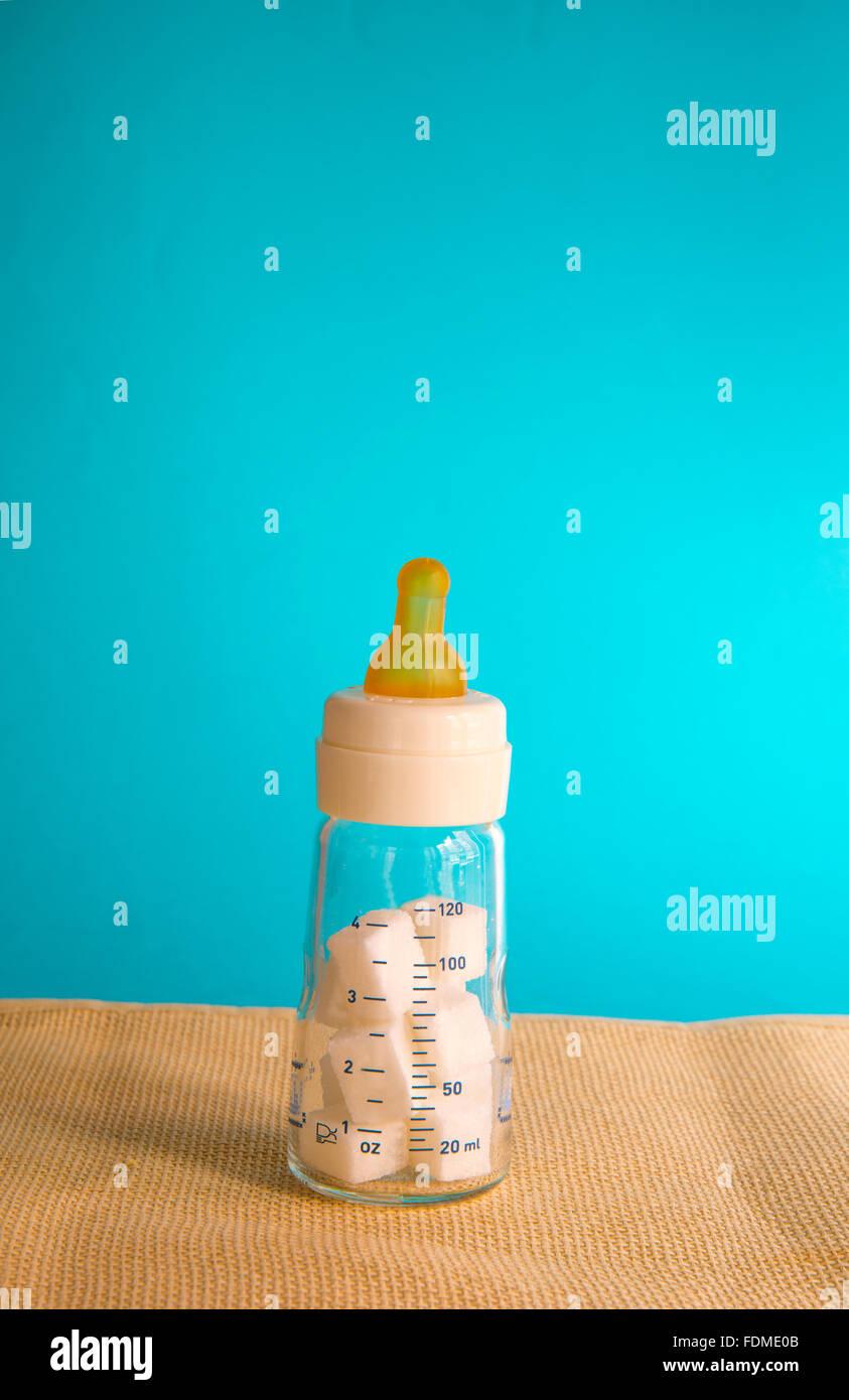 Bottle-feeding with lump sugar. - Stock Image