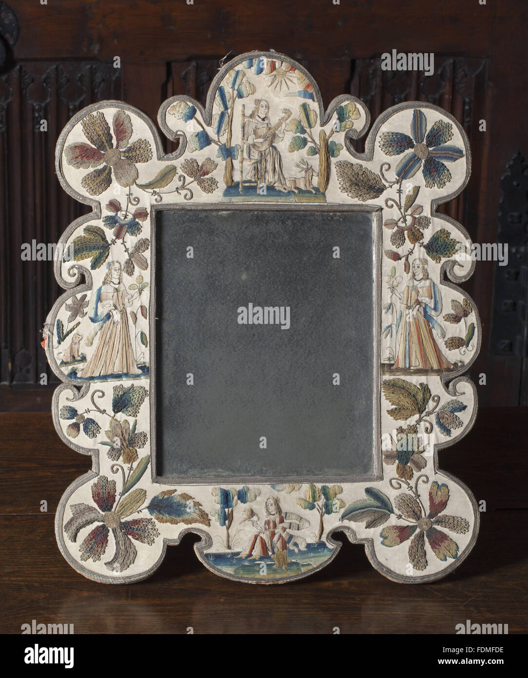 Mirror in shaped needlework frame at Melford Hall, Suffolk. Frame of embroidered figures, flowers, including four - Stock Image