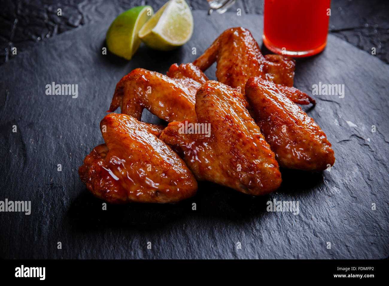 fried chicken wings on a black stone - Stock Image