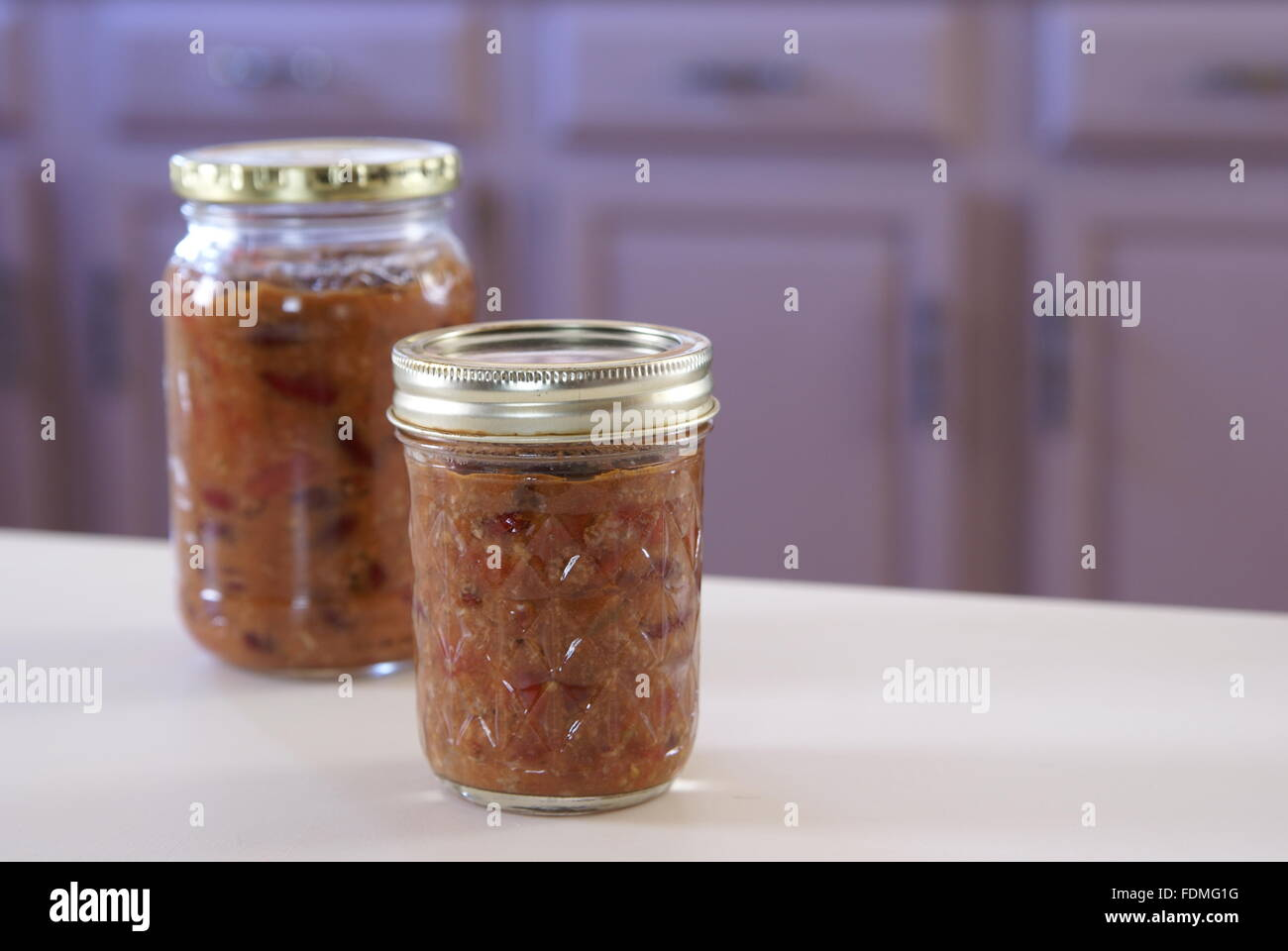 Homemade chili in glass canning jars in a home kitchen.