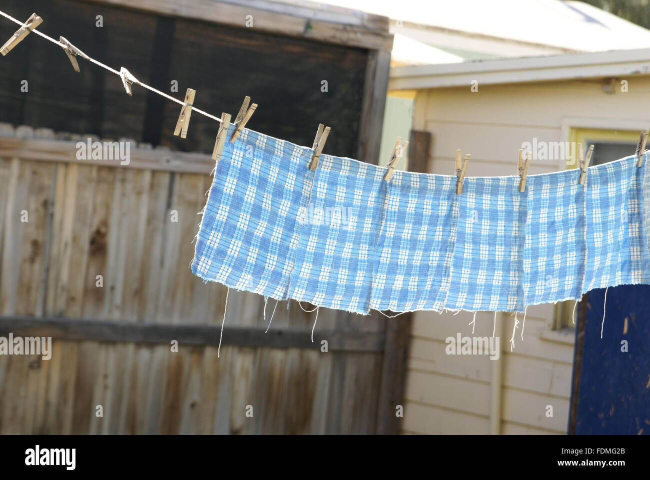 Blue gingham homemade hand towels hanging on an outdoor clothesline. - Stock Image