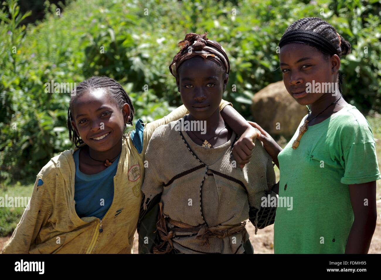 Three girls pose for a photograph on the side of a road through the mountains near Arba Minch in Ethiopia Stock Photo
