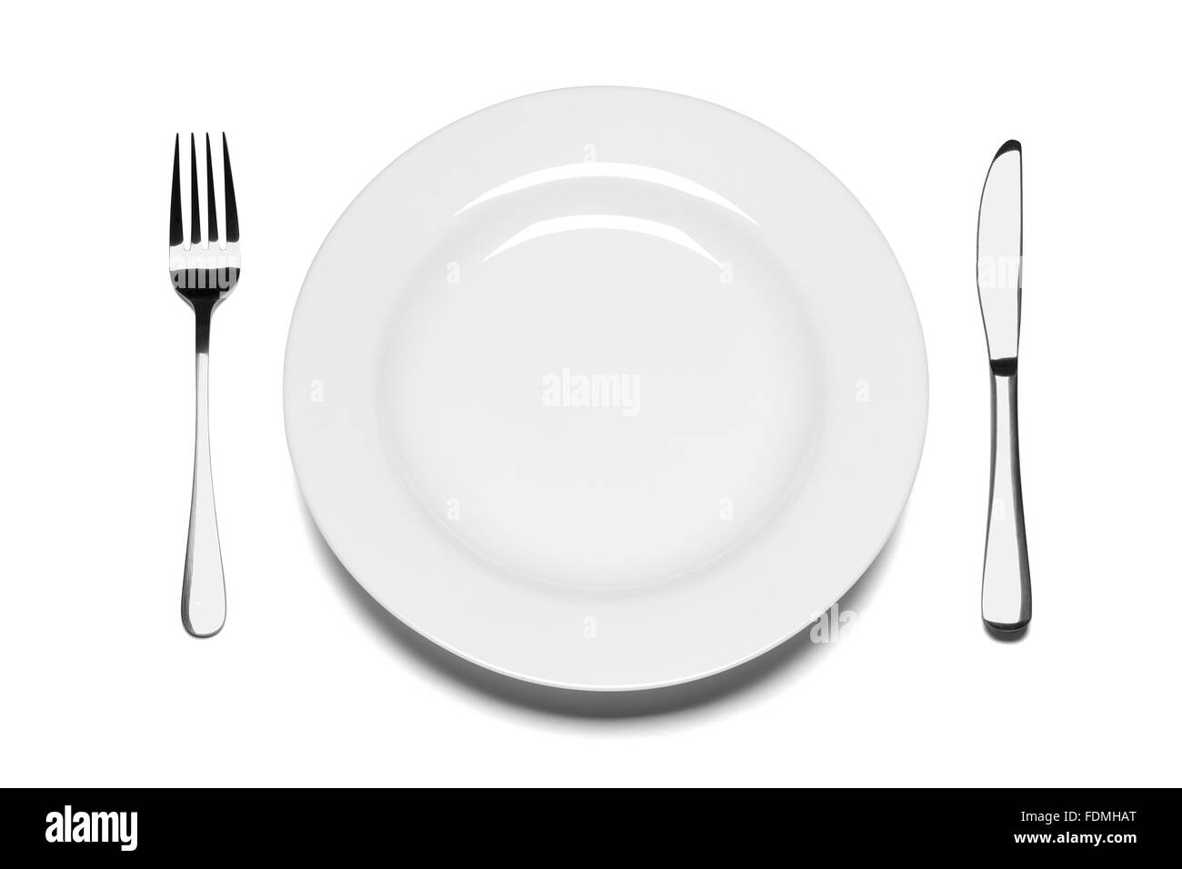 Empty plate with fork and knife isolated on the white background. - Stock Image