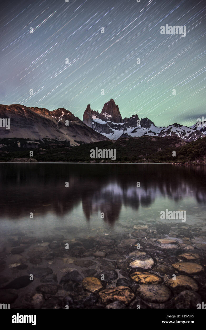 Stars in the sky streaked under the effect of long exposure and reflection of Mount Fitz Roy in lake - Stock Image