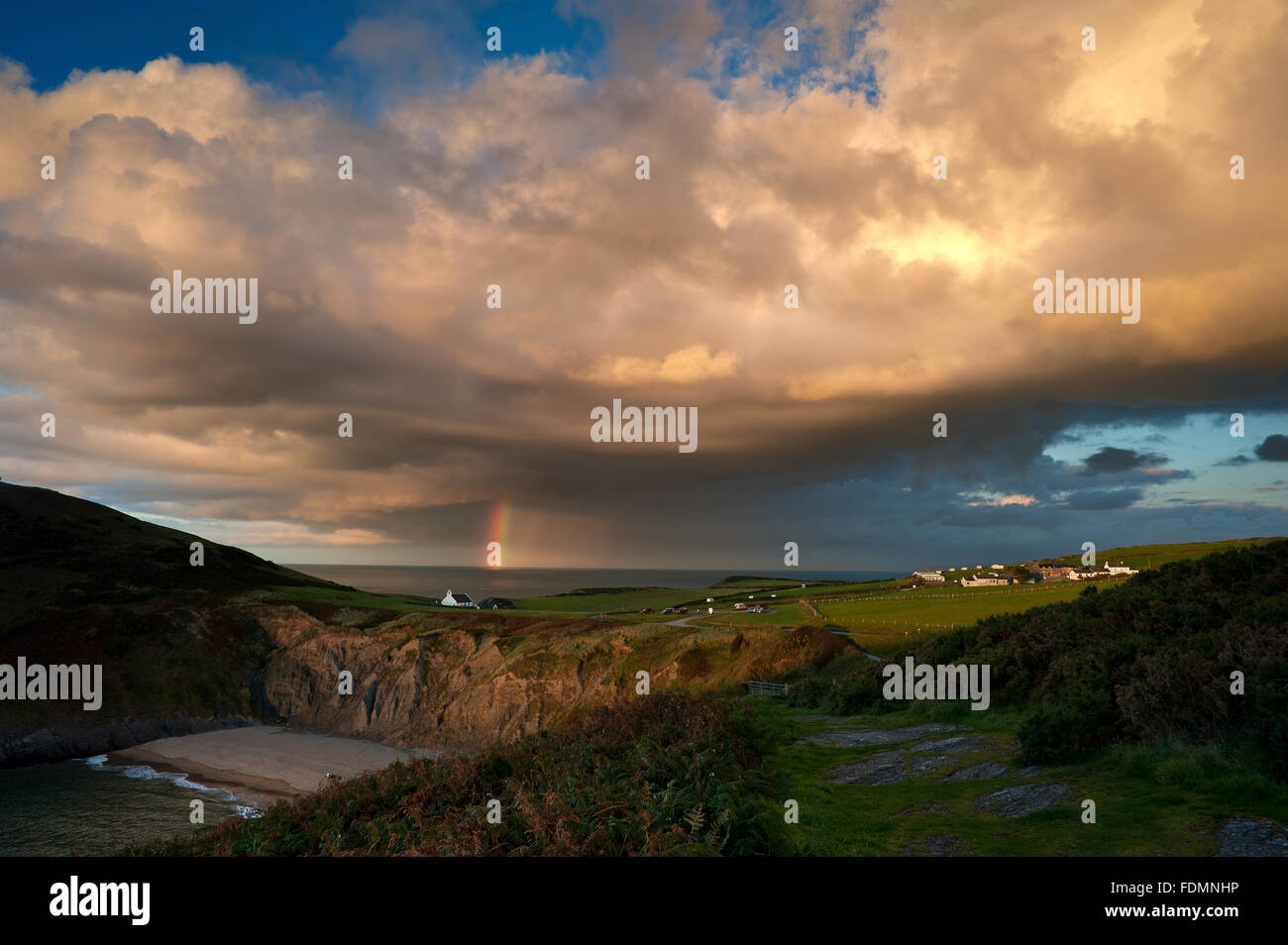 Rainbow over the Church of the Holy Cross, Mwnt, Ceredigion, West Wales - Stock Image