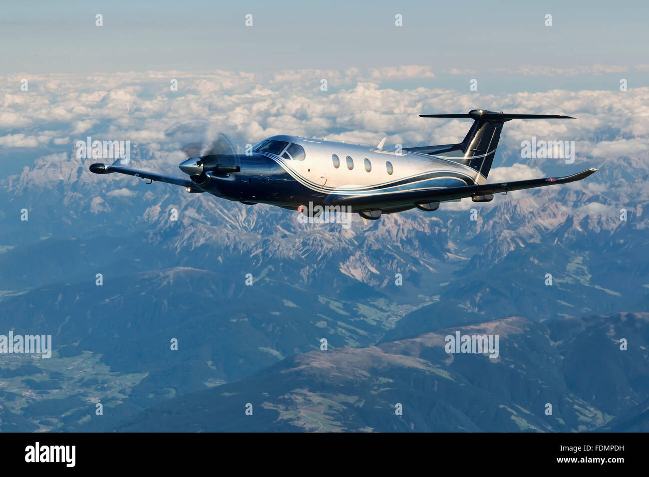 Single-engine turboprop aircraft flying over the Alps in Austria. - Stock Image