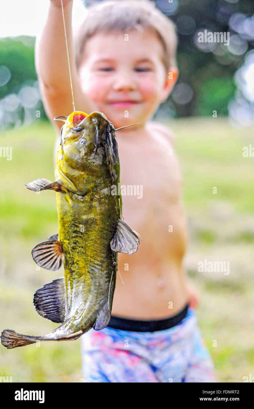 child holding first fish - Stock Image