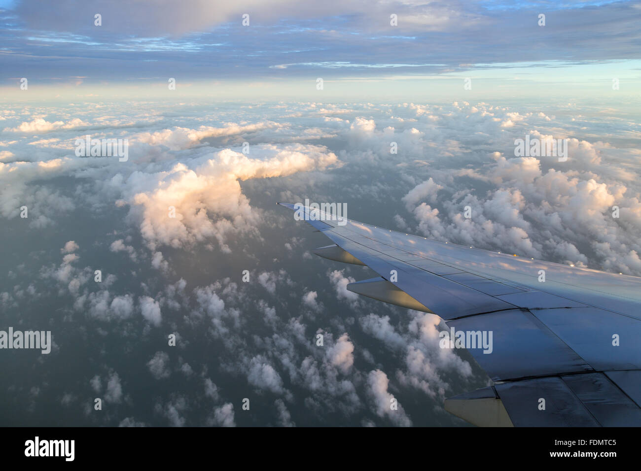 View of cloudy sky and airplane wing in the morning. - Stock Image