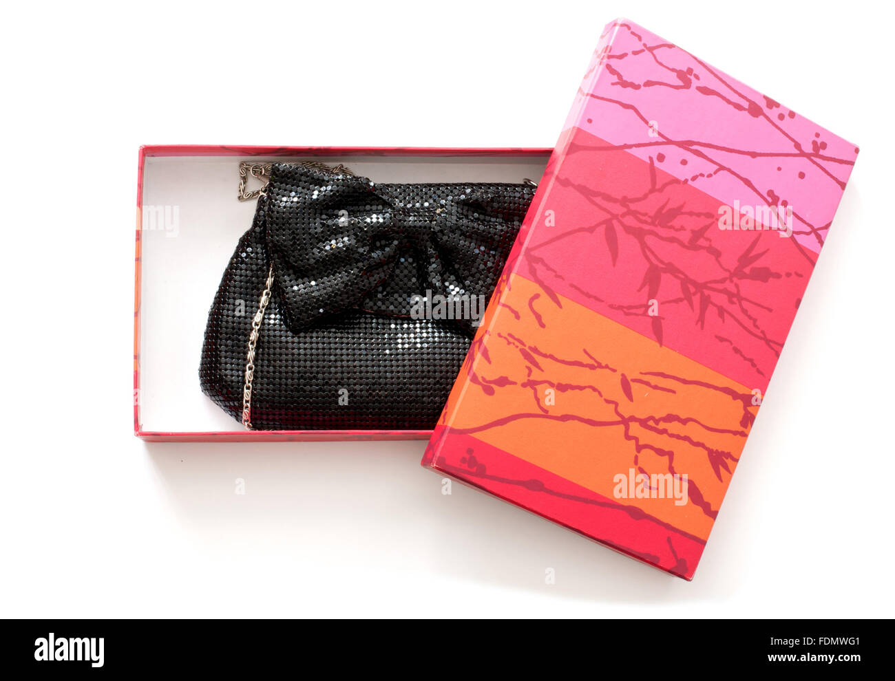 Isolated clutch bag in red and pink gift box over white - Stock Image