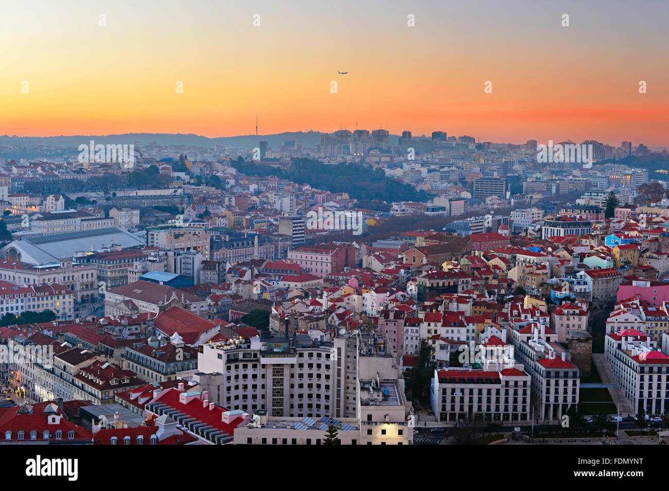 Airplane flying over the Lisbon at beautiful sunset. Portugal - Stock Image