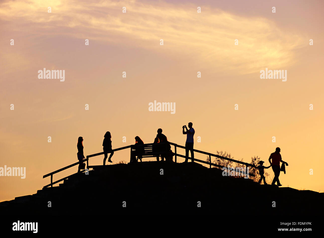 Silhouette of a people on a hill viewpoint at sunset - Stock Image