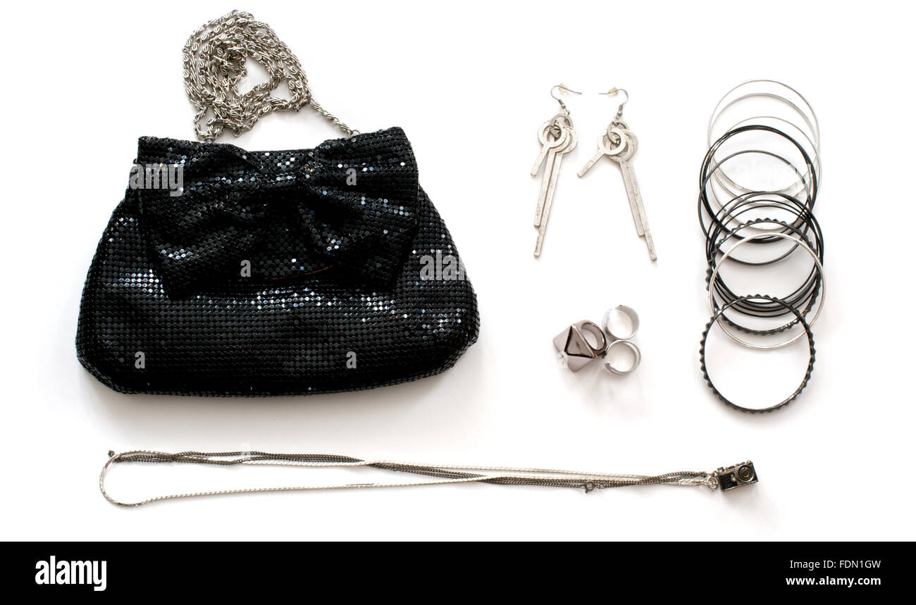 Isolated black clutch bag with accessories in rock style over white - Stock Image