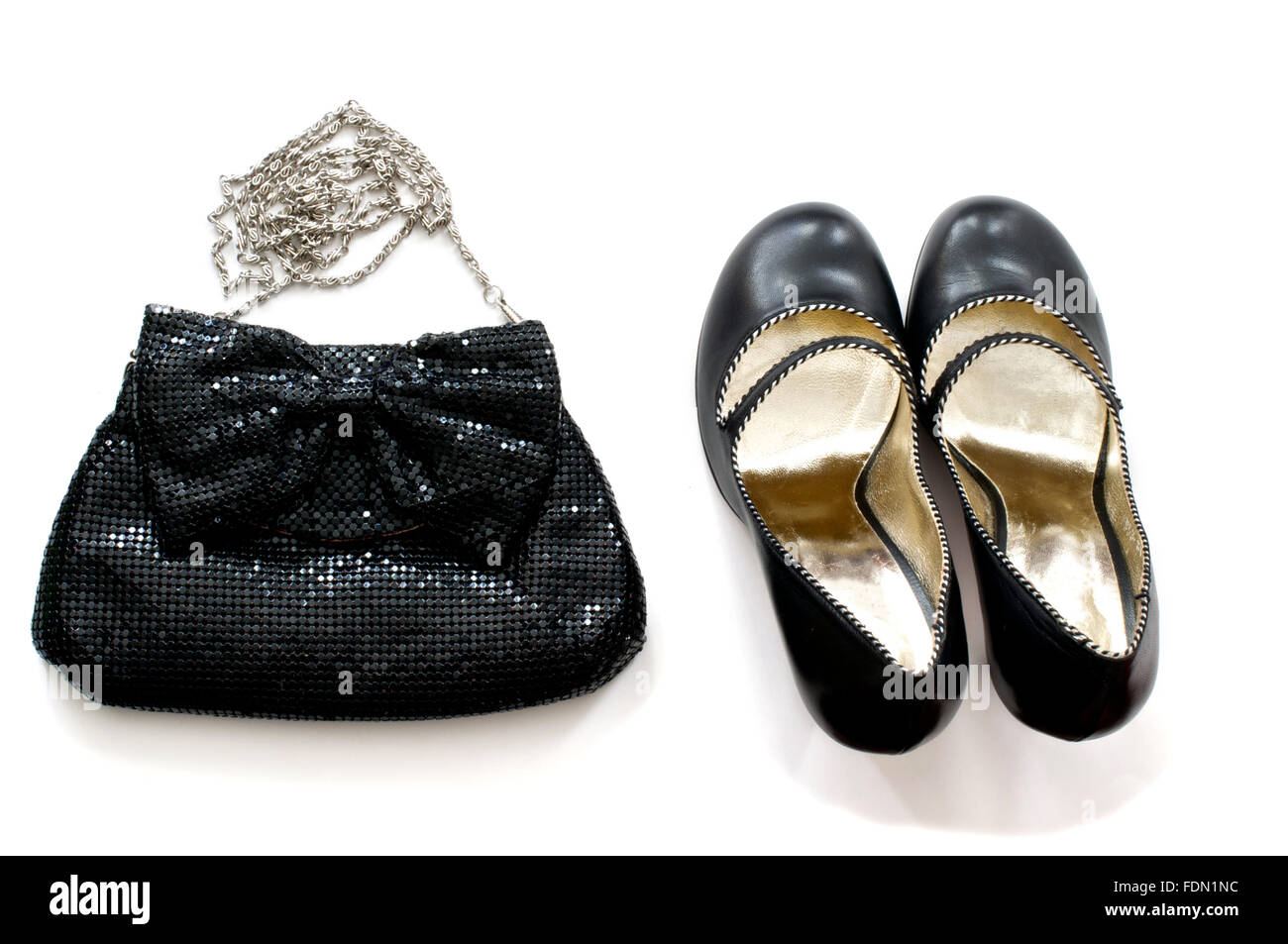 Isolated black clutch bag with high heels shoes over white - Stock Image