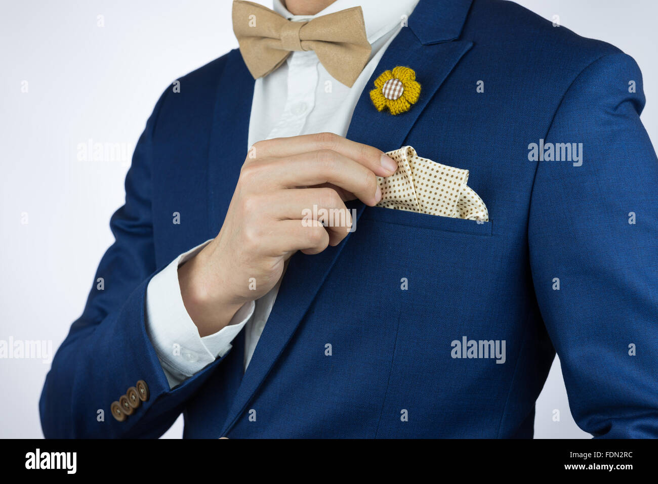 Man in blue suit with coffee cream bowtie color, flower brooch, and dot pattern pocket square, close up Stock Photo